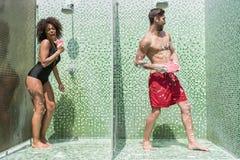 Διασκεδάζοντας νέα διασκέδαση ζευγών ταυτόχρονα στους κοντινούς θαλαμίσκους ντους στοκ εικόνες με δικαίωμα ελεύθερης χρήσης