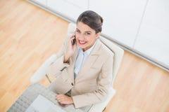 Διασκεδασμένη έξυπνη καφετιά μαλλιαρή επιχειρηματίας που κάνει ένα τηλεφώνημα Στοκ Φωτογραφίες