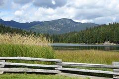 Διασπασμένα ξύλινα πλαίσια φρακτών μια σκηνή λιμνών και βουνών Στοκ Εικόνα