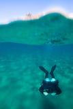Διασπασμένη φωτογραφία άποψης με την αρσενική κολύμβηση δυτών σκαφάνδρων κάτω από το νερό Στοκ φωτογραφία με δικαίωμα ελεύθερης χρήσης