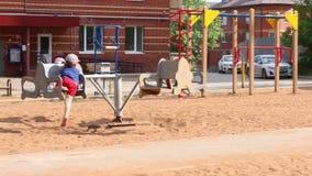 Διασταύρωση κυκλικής κυκλοφορίας γύρου αγοριών και μικρών κοριτσιών στην παιδική χαρά στη θερινή ημέρα φιλμ μικρού μήκους