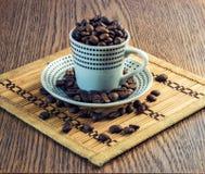 Διαστιγμένο φλυτζάνι που γεμίζουν με τα φασόλια καφέ που στέκονται σε ένα πιάτο Στοκ εικόνες με δικαίωμα ελεύθερης χρήσης