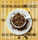 Διαστιγμένο φλυτζάνι που γεμίζουν με τα φασόλια καφέ που στέκονται σε ένα πιάτο Στοκ Φωτογραφίες