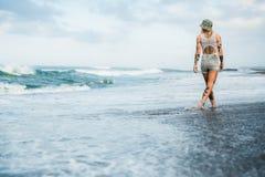 Διαστισμένη γυναίκα που περπατά στην παραλία Στοκ Φωτογραφίες