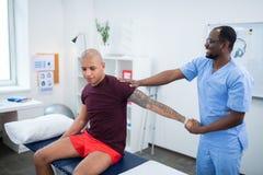 Διαστισμένος αθλητικός τύπος που απολαμβάνει το χρόνο με τον ευχάριστο φυσιοθεραπευτή στοκ εικόνες