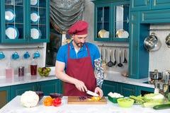 Διαστισμένο άτομο στην ποδιά και ΚΑΠ που κόβει την κίτρινη πάπρικα από το μαχαίρι Μάγειρας που μαγειρεύει τη φυτική σαλάτα με το  Στοκ Φωτογραφία
