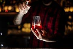 Διαστισμένο ψέκασμα μπάρμαν πικρό στο γυαλί με το κόκκινο γλυκό κοκτέιλ στοκ εικόνες