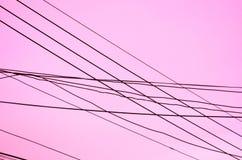 Διασχισμένα καλώδια πέρα από ένα ρόδινο υπόβαθρο Στοκ φωτογραφία με δικαίωμα ελεύθερης χρήσης