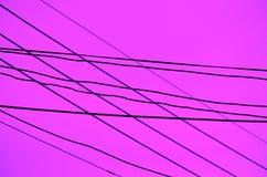 Διασχισμένα καλώδια πέρα από ένα σκοτεινό lavender υπόβαθρο στοκ εικόνες