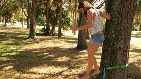 ΔΙΑΣ, ΦΛΩΡΙΔΑ ΗΠΑ - 17 ΙΟΥΝΊΟΥ 2017 Νέα γυναίκα που κάνει το slackline άσκησης σε ένα δημόσιο πάρκο στη Φλώριδα στοκ εικόνες με δικαίωμα ελεύθερης χρήσης
