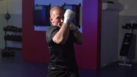 Διατρήσεις τραίνων μπόξερ στη γυμναστική, σε αργή κίνηση Πάλη άσκησης μαχητών με τη σκιά απόθεμα βίντεο