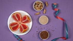 Διατροφή έννοιας - υγιή τρόφιμα με το γκρέιπφρουτ, το φυστίκι, το σουσάμι, τους σπόρους λιναριού και τη μέτρηση της ταινίας στο π στοκ εικόνα με δικαίωμα ελεύθερης χρήσης