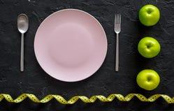 Διατροφή αδυνατίσματος Κενά πιάτο, μήλα και μέτρηση της ταινίας στο μαύρο πρότυπο άποψης υποβάθρου τοπ Στοκ Εικόνα