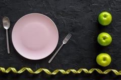 Διατροφή αδυνατίσματος Κενά πιάτο, μήλα και μέτρηση της ταινίας στο μαύρο πρότυπο άποψης υποβάθρου τοπ Στοκ Εικόνες
