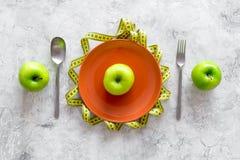 Διατροφή αδυνατίσματος Apple στο πιάτο και τη μέτρηση της ταινίας στην γκρίζα τοπ άποψη υποβάθρου πετρών Στοκ εικόνα με δικαίωμα ελεύθερης χρήσης