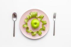 Διατροφή αδυνατίσματος Apple στο πιάτο και τη μέτρηση της ταινίας στην άσπρη τοπ άποψη υποβάθρου Στοκ Εικόνα
