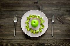 Διατροφή αδυνατίσματος Apple στο πιάτο και τη μέτρηση της ταινίας στην ξύλινη τοπ άποψη υποβάθρου Στοκ φωτογραφία με δικαίωμα ελεύθερης χρήσης