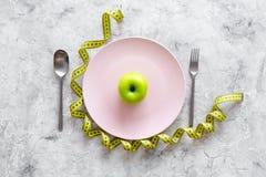 Διατροφή αδυνατίσματος Apple στο πιάτο και τη μέτρηση της ταινίας στην γκρίζα τοπ άποψη υποβάθρου πετρών Στοκ Φωτογραφία