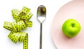 Διατροφή αδυνατίσματος Apple στο πιάτο και τη μέτρηση της ταινίας στην άσπρη τοπ άποψη υποβάθρου Στοκ Εικόνες
