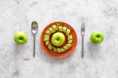 Διατροφή αδυνατίσματος Apple στο πιάτο και τη μέτρηση της ταινίας στην γκρίζα τοπ άποψη υποβάθρου πετρών Στοκ φωτογραφία με δικαίωμα ελεύθερης χρήσης
