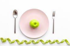 Διατροφή αδυνατίσματος Apple στο πιάτο και τη μέτρηση της ταινίας στην άσπρη τοπ άποψη υποβάθρου Στοκ φωτογραφίες με δικαίωμα ελεύθερης χρήσης