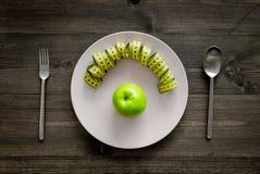 Διατροφή αδυνατίσματος Apple στο πιάτο και τη μέτρηση της ταινίας στην ξύλινη τοπ άποψη υποβάθρου Στοκ Φωτογραφίες