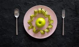 Διατροφή αδυνατίσματος Apple στο πιάτο και τη μέτρηση της ταινίας στη μαύρη τοπ άποψη υποβάθρου Στοκ φωτογραφίες με δικαίωμα ελεύθερης χρήσης
