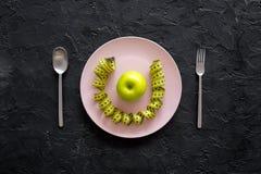 Διατροφή αδυνατίσματος Apple στο πιάτο και τη μέτρηση της ταινίας στη μαύρη τοπ άποψη υποβάθρου Στοκ φωτογραφία με δικαίωμα ελεύθερης χρήσης