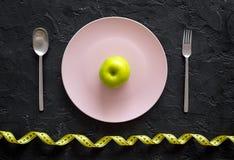Διατροφή αδυνατίσματος Apple στο πιάτο και τη μέτρηση της ταινίας στη μαύρη τοπ άποψη υποβάθρου Στοκ εικόνες με δικαίωμα ελεύθερης χρήσης