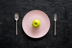 Διατροφή αδυνατίσματος Apple στο πιάτο στη μαύρη τοπ άποψη υποβάθρου Στοκ Φωτογραφίες