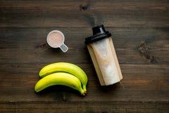 Διατροφή για το workout με το πρωτεϊνικό κοκτέιλ και την μπανάνα στο ξύλινο πρότυπο άποψης υποβάθρου τοπ στοκ φωτογραφία