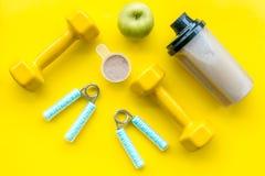 Διατροφή για το workout με το πρωτεϊνικό κοκτέιλ και τους φραγμούς στο κίτρινο πρότυπο άποψης υποβάθρου τοπ στοκ φωτογραφία