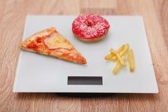 Διατροφή, γρήγορο φαγητό στην κλίμακα Ανθυγειινό άχρηστο φαγητό παχυσαρκία στοκ εικόνα