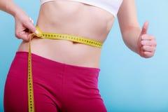 Διατροφή. Κατάλληλο κορίτσι γυναικών ικανότητας με την ταινία μέτρου που μετρά τη μέση της στοκ φωτογραφία με δικαίωμα ελεύθερης χρήσης
