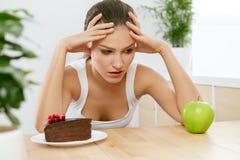 διατροφή σιτηρεσίου Γυναίκα που επιλέγει μεταξύ του κέικ και της Apple Στοκ φωτογραφία με δικαίωμα ελεύθερης χρήσης