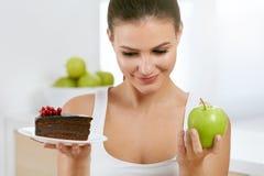 διατροφή σιτηρεσίου Γυναίκα που επιλέγει μεταξύ του κέικ και της Apple Στοκ Εικόνα