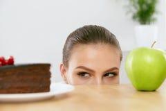 διατροφή σιτηρεσίου Γυναίκα που επιλέγει μεταξύ του κέικ και της Apple Στοκ Εικόνες