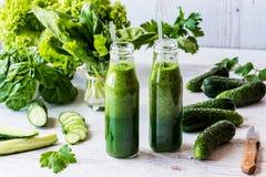 Διατροφή Detox Δύο μικρά μπουκάλια των φρέσκων πράσινων καταφερτζήδων με τα συστατικά σε ένα ελαφρύ ξύλινο υπόβαθρο Στοκ εικόνα με δικαίωμα ελεύθερης χρήσης
