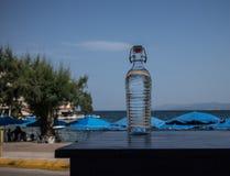 Διαφανές μπουκάλι με το υπόβαθρο νερού και ουρανού στοκ φωτογραφίες