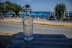 Διαφανές μπουκάλι με το υπόβαθρο νερού και ουρανού στοκ εικόνες με δικαίωμα ελεύθερης χρήσης