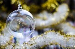 Διαφανές παιχνίδι Χριστουγέννων γυαλιού με την κίτρινη κινηματογράφηση σε πρώτο πλάνο γιρλαντών στοκ φωτογραφία με δικαίωμα ελεύθερης χρήσης