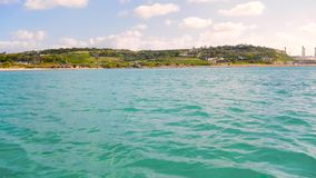 Διαφανές τυρκουάζ νερό στο πρώτο πλάνο, η θάλασσα Μικρή παραλιακή πόλη με την πρασινάδα, δέντρα, πράσινα, βράχοι, φύση απόθεμα βίντεο
