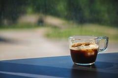 Διαφανές φλυτζάνι γυαλιού του καφέ πάγου που τοποθετείται σε ένα σκοτεινό ξύλινο lami στοκ φωτογραφία με δικαίωμα ελεύθερης χρήσης