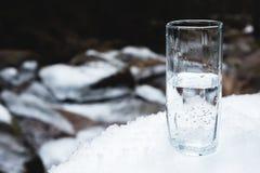 Διαφανής ένας γυαλί/γυαλί με την κατανάλωση του νερού βουνών στέκεται στο χιόνι σε ένα κλίμα ενός καθαρού ποταμού βουνών Στοκ φωτογραφία με δικαίωμα ελεύθερης χρήσης