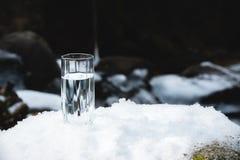 Διαφανής ένας γυαλί/γυαλί με την κατανάλωση του νερού βουνών στέκεται στο χιόνι σε ένα κλίμα ενός καθαρού βουνού παγετού Στοκ Φωτογραφία