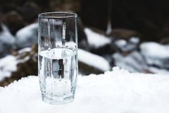 Διαφανής ένας γυαλί/γυαλί με την κατανάλωση του νερού βουνών στέκεται στο χιόνι σε ένα κλίμα ενός καθαρού ποταμού βουνών Στοκ Φωτογραφίες