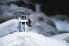 Διαφανής ένας γυαλί/γυαλί με την κατανάλωση του νερού βουνών στέκεται στο χιόνι σε ένα κλίμα ενός καθαρού βουνού παγετού Στοκ Εικόνες