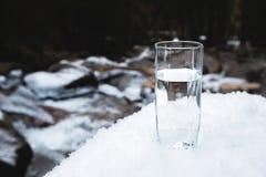 Διαφανής ένας γυαλί/γυαλί με την κατανάλωση του νερού βουνών στέκεται στο χιόνι σε ένα κλίμα ενός καθαρού βουνού παγετού Στοκ εικόνα με δικαίωμα ελεύθερης χρήσης