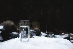 Διαφανής ένας γυαλί/γυαλί με την κατανάλωση του νερού βουνών στέκεται στο χιόνι σε ένα κλίμα ενός καθαρού ποταμού βουνών Στοκ Εικόνες