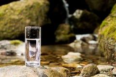 Διαφανής ένας γυαλί/γυαλί με το ορυκτό νερό ποταμού βουνών στέκεται σε μια πέτρα εκτός από τον κολπίσκο ποταμών βουνών Στοκ φωτογραφία με δικαίωμα ελεύθερης χρήσης
